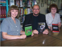 Author and Ashland native Thomas M. Malafarina sits with Ashland Public Library librarians Rene Hardnock left and Ann Helwig. They are holding the three books he authored, which were donated to the library Friday.