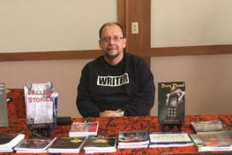 Behind my books and ready to sign